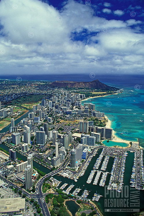 Impressive aerial shot of Ala Wai boat harbor, Waikiki beach and hotels and Diamond Head crater. Huge white clouds drift above the blue Pacific.