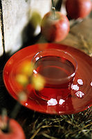 A glass bowl filled with honey on a red plate decorates the rustic table which is also strewn with hay and red apples