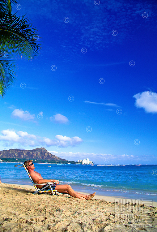 A man in swim trunks relaxes in a lounge chair on the sand at Waikiki Beach with Diamond Head in the background.
