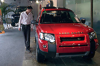 A potential customer looks at a Land Rover at the Land Rover showroom in Beijing, China..