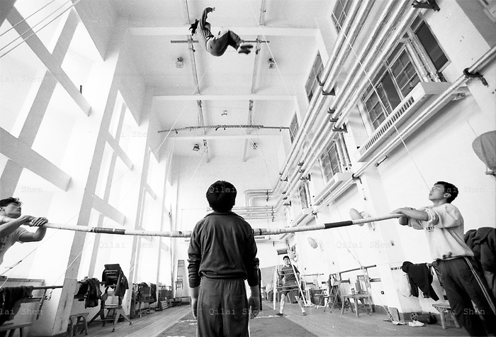 "QSFeature01Acrobats006 20010414 SHANGHAI, CHINA: While her partner watches on, a female student practices the highly dangerous manuvres of the ""Pole Bounce"" at the Shanghai Circus School in Shanghai, China 14 April 2001. Traditional entertaiment such as acrobatic shows are loosing audiences and popularity in China, and the students will likely face a tough time when they finally finish six years of grueling training..Photo by: Qilai Shen"