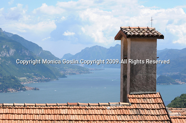 A view of Lake Como, Italy with a small church roof and bell tower in the foreground.