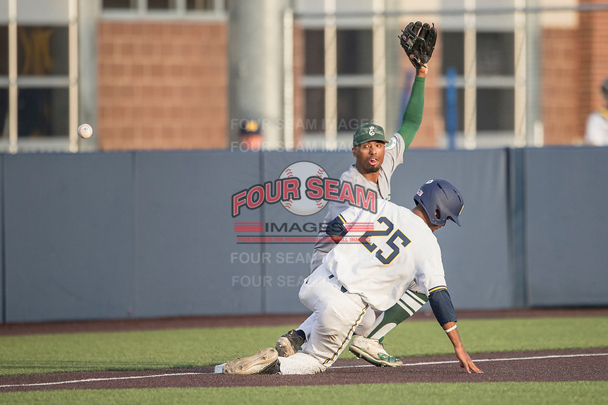Eastern Michigan Eagles third baseman Marquise Gill (4) misses a throw from the outfield as Michigan Wolverines baserunner Johnny Slater (25) slides in during the NCAA baseball game on May 16, 2017 at Ray Fisher Stadium in Ann Arbor, Michigan. Michigan defeated Eastern Michigan 12-4. (Andrew Woolley/Four Seam Images)