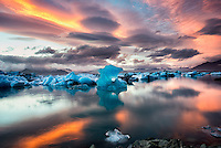 """Iceland, Jokulsarlon, Glacier lagoon. Skaftafell National Park.  Iceland, lying just below the Arctic Circle, is one of the fastest-warming places on the earth. According to the Daily Climate, the 300 some glaciers that cover 10 percent of the island are losing an average of 11 billion tons of ice a year. On this assignment I had just traveled Iceland and Greenland for the Hurtigruten cruise line, photographing the various incarnations of ice in all its magnificence. Once off the ship I drove across Iceland and one evening ended up in """"Iceberg Alley."""" I watched as this iceberg flipped over and for the next three and a half hours photographed this ever-changing scene as the sun played out its captivating lightshow."""