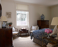 Another small guest bedroom continues the blue and white theme of other rooms