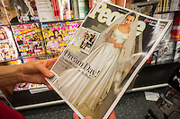 A reader browses a copy of People magazine featuring the wedding of Angelina Jolie and Brad Pitt in New York on Wednesday, September 3, 2014. People is reported to have paid almost $2 million for the U.S. rights with Hello buying the European rights. In 2008 photos of the couple's twin children went for $11 million. (© Richard B. Levine)