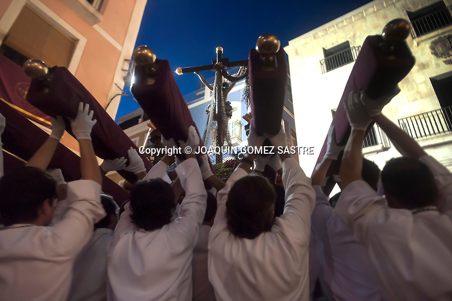 The costaleros of the Brotherhood of the Holy Cross step rise in  procession of Christ the sea