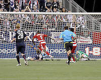New England Revolution defender Darrius Barnes (25) slides to save the ball from FC Dallas forward Jeff Cunningham(9) after New England Revolution goalkeeper Preston Burpo (24) deflects a shot at goal.  The New England Revolution drew FC Dallas 1-1, at Gillette Stadium on May 1, 2010