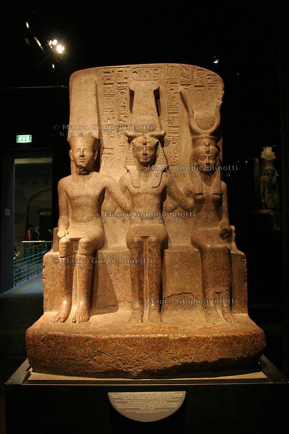 ITALIA - Torino - Museo Egizio  Il faraone Ramesse II coon il dio Amon e la dea Mut; il faraone è seduto con il dio e la moglie, protettori e garanti della dinastia Il faraone indossa la corona atef composta dal disco solare tra corna dell'ariete sacro di Amon e dall'emblema della dea giustizia Maat....(granito rosa XIX dinastia regno di Ramesse II 1279-1213 ac tempio di Amon, Tebe)....red granyte XIX dynasty reign of Ramesses II 1279-1213 BC temple of Amon Thebes..the king is seated with the god Amon and his consort Mut both consdidered the protectors and guarantors of the New Kingdom royals.The king wears the atef-crown composed of the sundisk and Amun ram horns and teh Maat feathers of justice