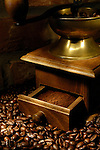 Arabica whole coffee beans and an old coffee grinder shining with gold under dramatic lighting Artistic still life