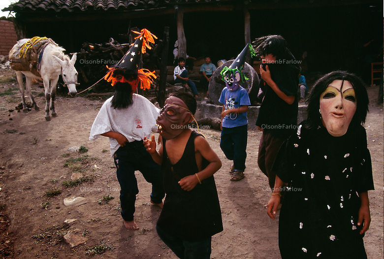 A blurring of cultures as children dance in the street wearing Halloween masks in celebration of Day of the Dead in the small town where families make mescal from agave plants.