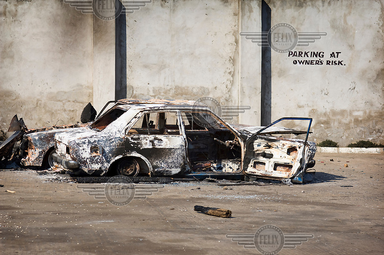 Burnt out vehicles in the car park of a looted petrol station, beneath the warning: 'Parking at owner's risk'. The economy had suffered as property and businesses were abandoned due to the civil unrest which followed disputed election results.