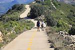 Two people on mountain path walk Coll de Rates, Tàrbena, Marina Alta, Alicante province, Spain