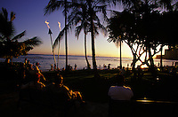 People seated on benches at Waikiki Beach at sunset with tiki torches lit