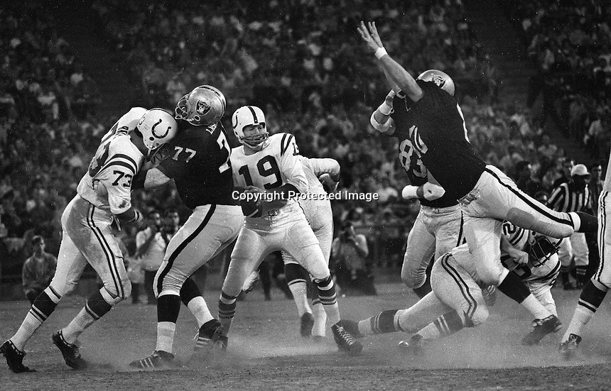 Oakland Raiders vs Baltimore Colts: QBJohnny Unitas is rushed by Ike Lassiter and Art Thoms. (photo by Ron Riesterer)