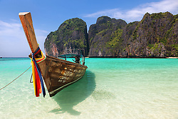A long tail boat rests in the emerald waters of Maya Bay, Koh Phi Phi, Thailand.