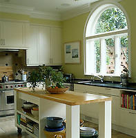 A fan-shaped window is the focus of the kitchen which is furnished with an island unit on wheels