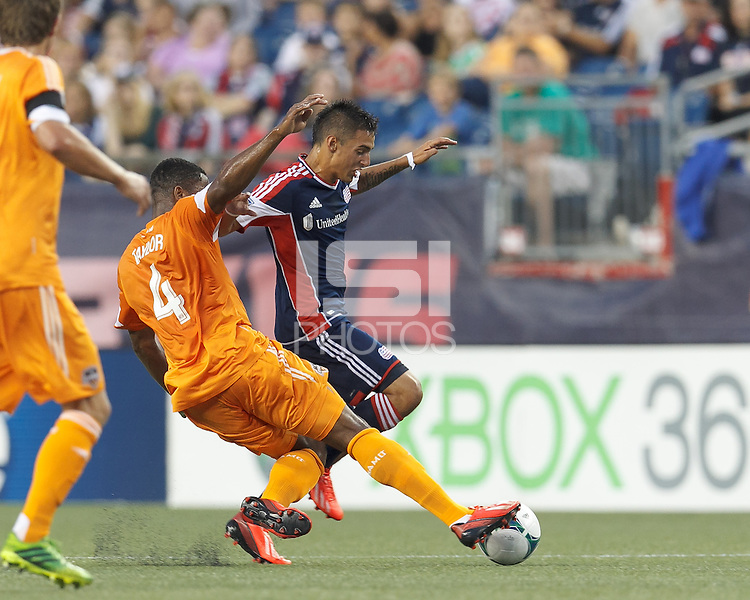 Houston Dynamo defender Jermaine Taylor (4) thwarts New England Revolution midfielder Diego Fagundez (14). In a Major League Soccer (MLS) match, Houston Dynamo (orange) defeated the New England Revolution (blue), 2-1, at Gillette Stadium on July 13, 2013.