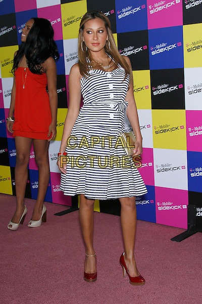 ADRIENNE BAILON of THE CHEETAH GIRLS.Attending the T-Mobile Sidekick iD Launch, .held at the T-Mobile Sidekick Lot,  Los Angeles, California, USA,13 April 2007..full length blue and white striped dress buttons red shoes.CAP/ADM/ZL.©Zach Lipp/AdMedia/Capital Pictures.