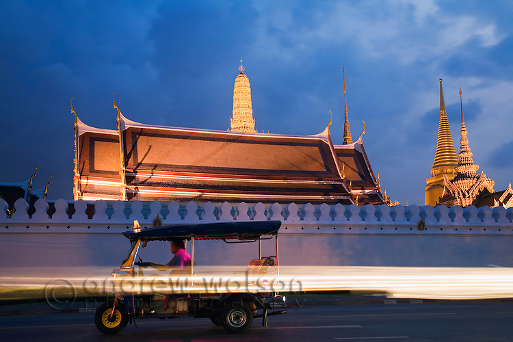 A tuk-tuk driver idles in front of Wat Phra Kaew and the walls of the Grand Palace in Bangkok, THAILAND.