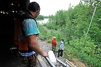 As conductor Charles Baldwin, left, looks on, John Lovert and Frannie Christensen plan their river trip down the Susitna River, visible in the background. The Alaska Railroad's Hurricane Turn is one of America's last true whistlestop trains.