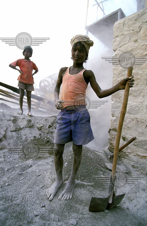 Young Dalit ( Untouchable) boys who work feeding granite blocks into stone crushing machines close to a rural quarry.