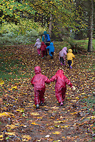 Fiddlehead students Amalie Brenner and Audette Laird, right, both 3, catch up with the rest of the group on a hike in the Washington Park Arboretum during Fiddleheads Forest School, a nature preschool.
