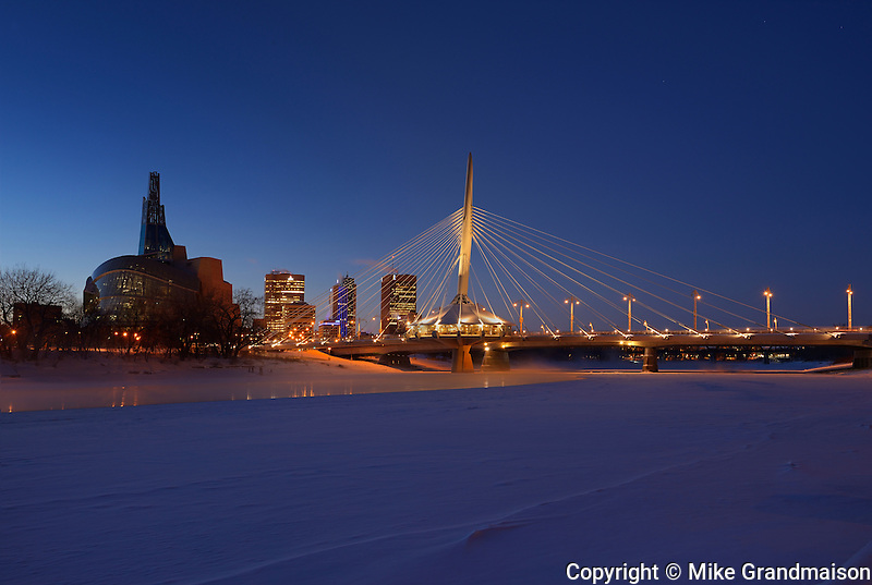 Winnipeg skyline with the Canadian Museum for Human Rights (CMHR) and the Esplanade Riel Bridge and the Red River in winter at dusk<br /> Winnipeg<br /> Manitoba<br /> Canada