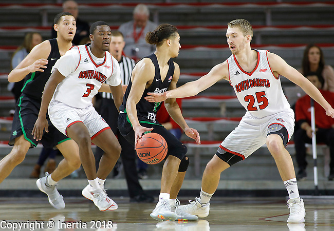 VERMILLION, SD: MARCH 14:  Ryan Woolridge #0 of North Texas dribbles between South Dakota defenders Triston Simpson #3 and Tyler Hagedorn #25 during the 2018 CBI Basketball Tournament at the Sanford Coyote Sports Center in Vermillion, S.D.  (Photo by DIck Carlson/Inertia)