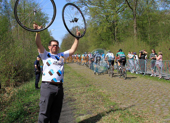 An AG2R team mechanic holds up spare wheels as riders race through the Forest of Arenberg on Pave Section 16 during the 109th edition of the Paris-Roubaix cycle race, 10th April 2011 (Photo by Eoin Clarke/NEWSFILE)