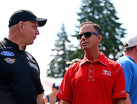 Aug. 2, 2014; Kent, WA, USA; NHRA top fuel dragster driver Steve Torrence (right) talking with funny car driver Tim Wilkerson during qualifying for the Northwest Nationals at Pacific Raceways. Mandatory Credit: Mark J. Rebilas-