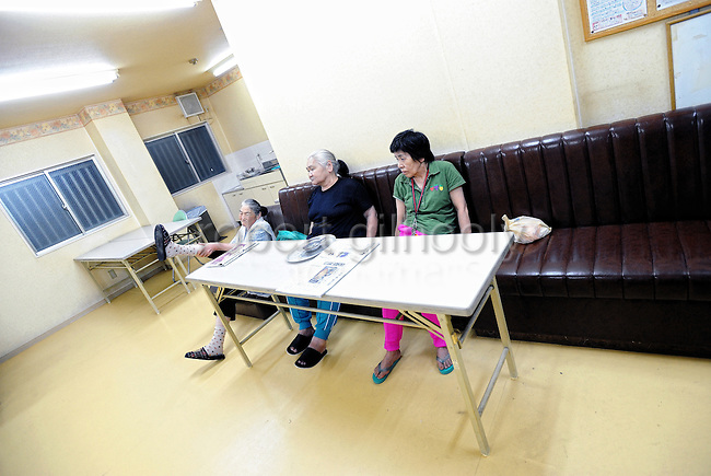 Three homeless women watch TV in the communal room of a former hotel specially adapted for the homeless community in the Kamagasaki district of Osaka, Japan. Elderly homeless aged 65 and over are eligible for special governmental benefits that allows them to stay in relatively more comfortable accommodation than their under-65 counterparts, which, in the central Osaka district of Kamagasaki, costs around 42,000 yen ($US320) a month and provides lodgers with communal bath and TV facilities and a 7 sq.-meter room -- barely big enough to fit a single bed and refrigerator.