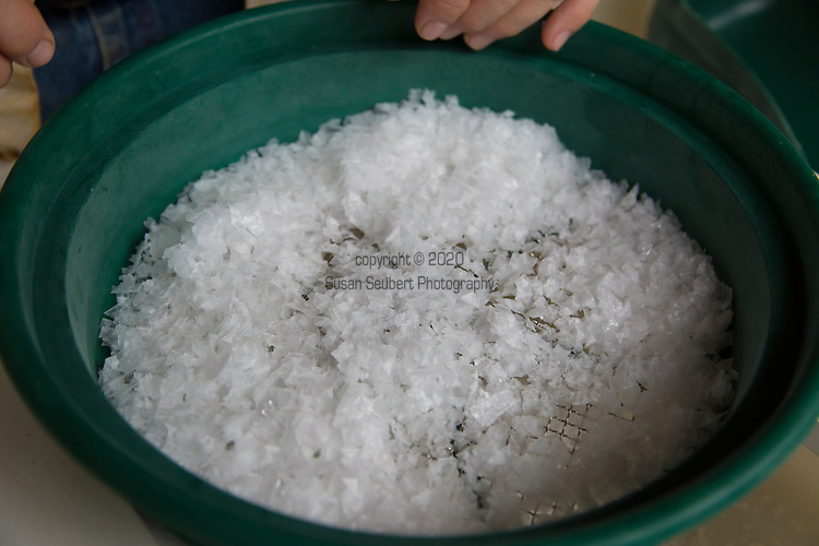 Jacobsen Salt Company in Netarts, Oregon, USA. The salt is harvested from sea water pumped from Netarts Bay in to their facility located on the shore of the bay. Jacobsen Salt was founded in 2011 by owner Ben Jacobsen.  Their main products are flake and kosher sea salts available for sale in their store in Portland, Oregon.  Contact Ben Jacobson sales@jacobsensalt.com or 503-473-3952. Pictured here is salt being sifted and blended by grade.