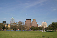 Woman flys a kite on perfect day on auditorium shores at Town Lake Austin.