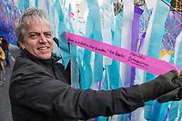 """Aufbau der Kunstinstallation """"Visions in Motion"""" des Kuenstler Patrick Shearn vor dem Brandenburger Tor anlaesslich der Feierlichkeiten zum 30. Jahrestag des Mauerfall am 9. November 1989.<br /> 30.000 Botschaften von Berlinern werden in einer Laenge von rund 150 Metern als Teppich aus bunten Faehnchen ueber der Strasse des 17. Juni schweben.<br /> Im Bild: Der Kuenstler Patrick Shearn aus Los Angeles haelt ein Faehnchen mit der Aufschrift """"Niemand hat die Absicht eine Mauer zu errichten. Erich Honecker"""". Das Zitat stammt jedoch vom ehemaligen DDR-Staatsratsvorsitzenden Walter Ulbricht und nicht Erich Honecker.<br /> 1.11.2019, Berlin<br /> Copyright: Christian-Ditsch.de<br /> [Inhaltsveraendernde Manipulation des Fotos nur nach ausdruecklicher Genehmigung des Fotografen. Vereinbarungen ueber Abtretung von Persoenlichkeitsrechten/Model Release der abgebildeten Person/Personen liegen nicht vor. NO MODEL RELEASE! Nur fuer Redaktionelle Zwecke. Don't publish without copyright Christian-Ditsch.de, Veroeffentlichung nur mit Fotografennennung, sowie gegen Honorar, MwSt. und Beleg. Konto: I N G - D i B a, IBAN DE58500105175400192269, BIC INGDDEFFXXX, Kontakt: post@christian-ditsch.de<br /> Bei der Bearbeitung der Dateiinformationen darf die Urheberkennzeichnung in den EXIF- und  IPTC-Daten nicht entfernt werden, diese sind in digitalen Medien nach §95c UrhG rechtlich geschuetzt. Der Urhebervermerk wird gemaess §13 UrhG verlangt.]"""