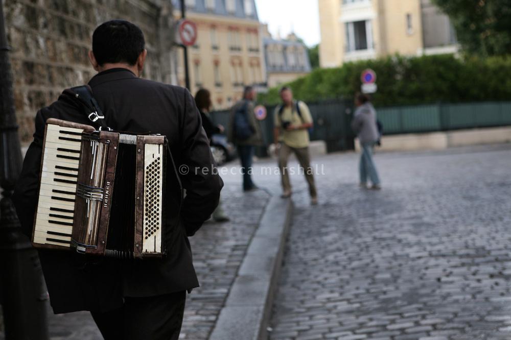 An accordionist walks through Montmartre, Paris, France, 15 September 2009