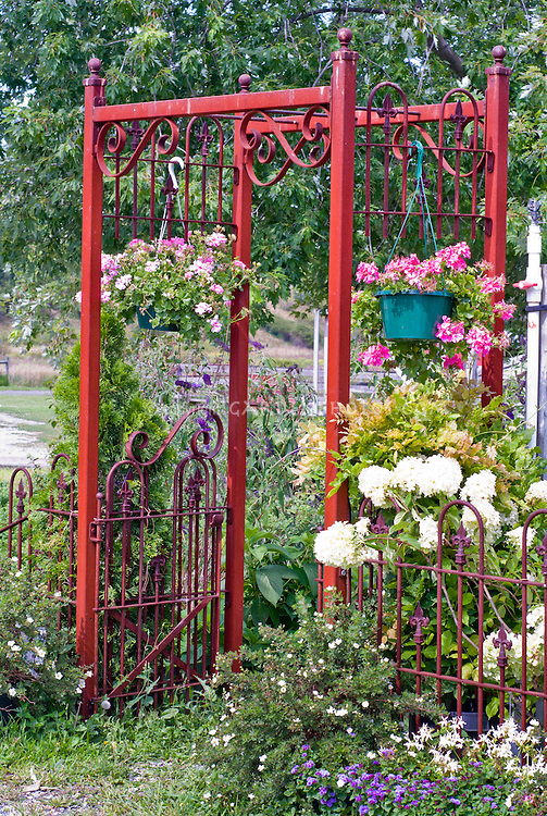 Rustic iron arbor trellis, hanging plants pots containers, hydrangea, lots of flowers for nice inviting entryway
