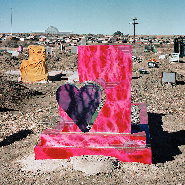 A gravestone in the shape of a heart and painted bright pink and purple in the Mamahabane township's cemetery.