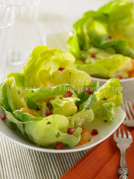 Two bowls of Butter Lettuce salad with pomegranate seeds and slices of orange.
