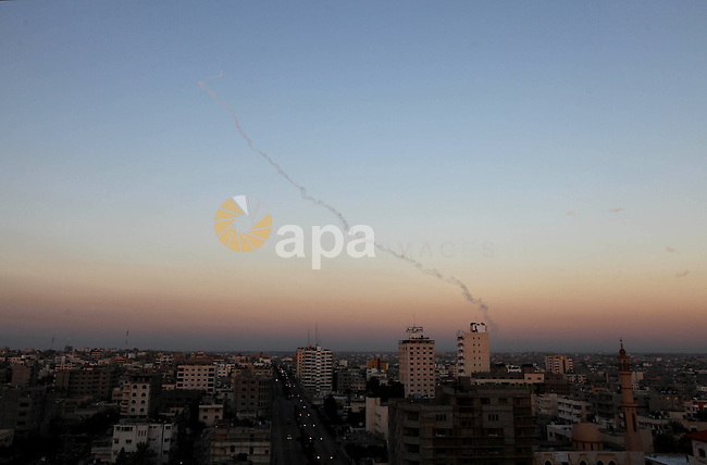 Three rockets fired by Palestinian militants at southern Israel leaves a thin trail of white smoke, seen between buildings in Gaza City, Thursday, Nov. 15, 2012. Militants in the Gaza Strip pounded southern Israel with rocket fire on Thursday, killing three people as the Israeli military pressed forward with a second day of intense air raids and naval attacks on militant targets. With Israel threatening to invade the Palestinian territory, the heaviest fighting between Israel and Hamas in four years showed no signs of letting up. Photo by Majdi Fathi