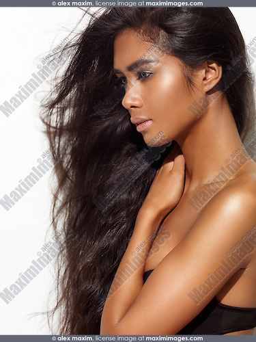 Profile beauty portrait of a young woman with dark skin and long brown hair