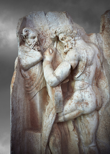 Close up of a Roman Sebasteion relief sculpture of  Herakles is preparing to wrestle the Libyan giant Antaios. Aphrodisias Museum, Aphrodisias, Turkey. Against a grey background.<br /> <br /> Herakles (left) is taking off his bow case to hang it on a pillar statue. Antaios (right) is binding up his head with ear protectors, next to him stands an oil basin used in the palaistra (wrestling ground). Antaios was a famous wrestler who challenged and killed all visitors to his country, until he was defeated by Herakles.