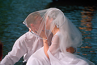 Saint Petersburg, Russia, June 2002..Newly-weds boating on a city canal. The mid-summer White Nights period when the sun sets only briefly is a time of festivals, entertainment and walks along the Neva River to watch the city bridges raise for shipping.