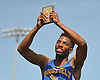 Roosevelt senior Joshua Stevenson acknowledges the cheers of the crowd after winning the boys' 400 meter intermediate hurdles event on his home field in the Nassau County Class A varsity track and field championships at Roosevelt High School on Friday, May 29, 2015.<br /> <br /> James Escher