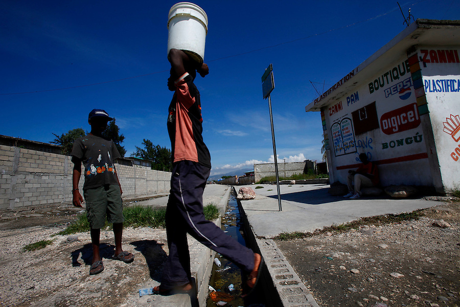 Nov 10, 2010 - Port-au-Prince, Haiti.A resident of the Cite Soleil area of Port-au-Prince, Haiti steps over a gutter filled with human waste as he carries water gathered from a well just yards away on Wednesday, November 10, 2010 as fears of a Cholera outbreak spread through the area just two days after cases of the infection were confirmed in the area, the poorest slum in Haiti's capital. Officials from the Pan American Health Organization warn that Haiti's cholera epidemic, spread primarily through consuming infected water and food, is likely to grow much larger in the wake of Hurricane Tomas.  (Credit Image: Brian Blanco/ZUMA Press)