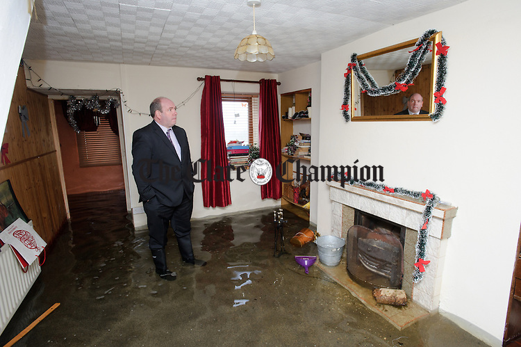 Councillor Gerry Finnerty in the living room of  Nancy Walsh's flooded home at Caherbroder, Gort adjacent to the M18 motorway.  Photograph by John Kelly.