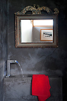 The walls of this small bathroom in a converted barn have been given a tadelakt paint effect which contrasts well with the antique gilt-framed mirror