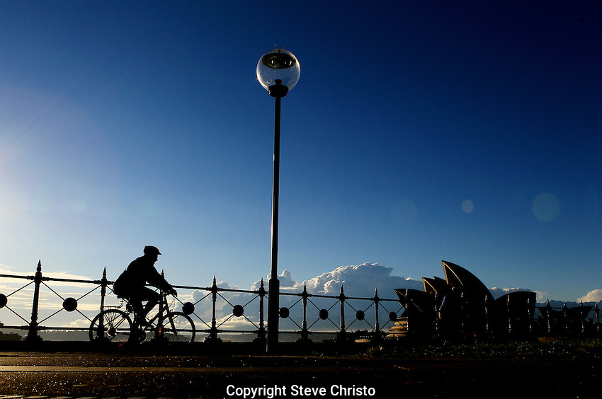 An early morning cyclist heads towards Circular Quay in front of the Sydney Opera House. Sydney Australia. Thursday May 3rd 2012 .(Photo Steve Christo).