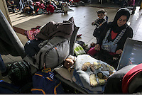 Pictured: A young migrant mother looks after her young baby at the passenger terminal Friday 26 February 2016<br /> Re: Hundreds of refugees that crossed the border from Turkey to the Greek islands, have arrived at the port of Piraeus near Athens, Greece