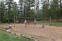 Photo story of Philmont Scout Ranch in Cimarron, New Mexico, taken during a Boy Scout Troop backpack trip in the summer of 2013. Photo is part of a comprehensive picture package which shows in-depth photography of a BSA Ventures crew on a trek. In this photo, BSA Venture crew members play a pick up game of volleyball within the wooded area of  Cimarroncito Camp in the backcountry at Philmont Scout Ranch.  <br /> <br /> The  Photo by travel photograph: PatrickschneiderPhoto.com
